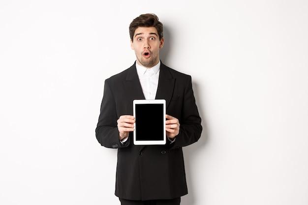 Immagine di un bell'uomo sorpreso in abito nero, che mostra lo schermo del tablet digitale e sembra stupito, in piedi su sfondo bianco