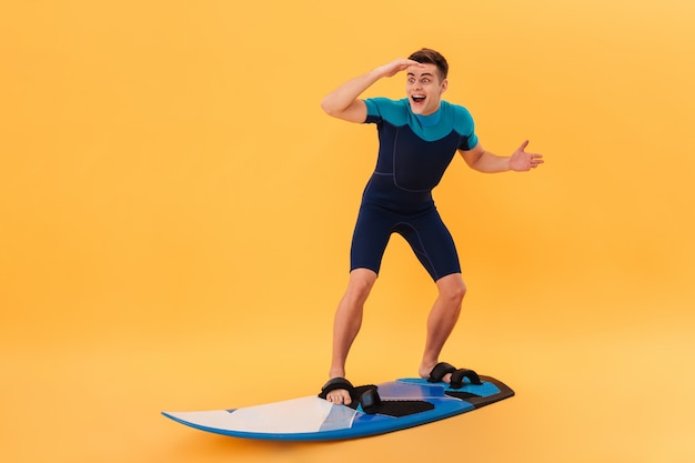 Image of surprised happy surfer in wetsuit using surfboard like on wave and looking away