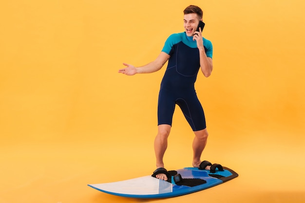 Image of surprised happy surfer in wetsuit using surfboard and talking by smartphone