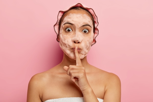 Image of surprised korean lady with soap bubbles on face, makes silence gesture, tells beauty secret, cleans and exfoliates skin, has cosmetic procedures during free time, takes care of herself