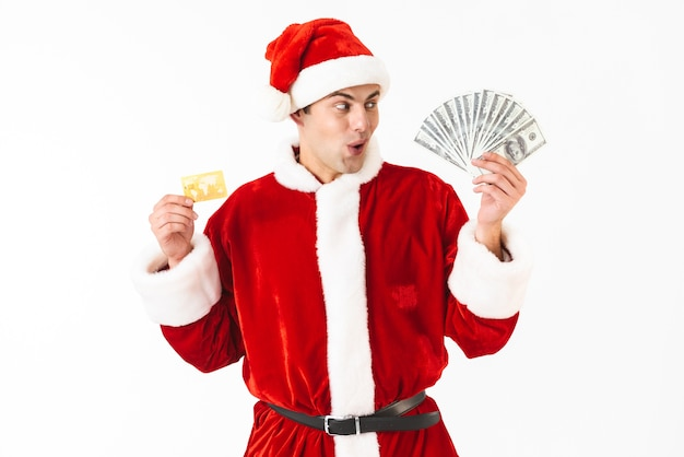 Image of surprised man 30s in santa claus costume holding dollar bills and credit card