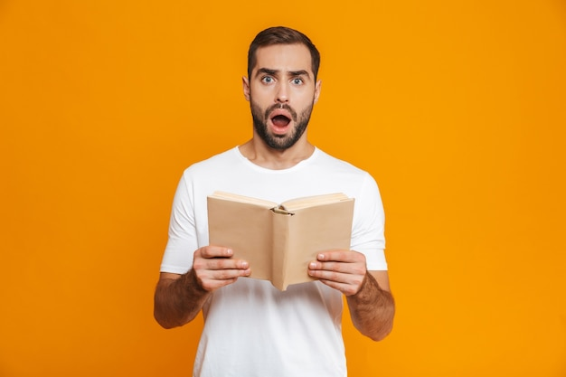 Image of surprised man 30s in white t-shirt holding and reading book, isolated