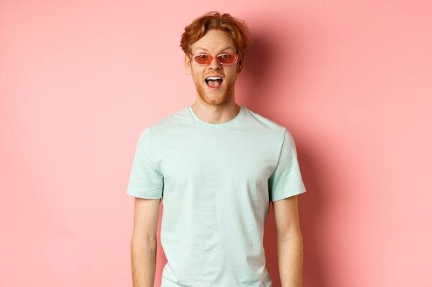 Image of surprised redhead man on vacation, wearing sunglasses with summer t-shirt, open mouth and saying wow amazed, standing over pink background.