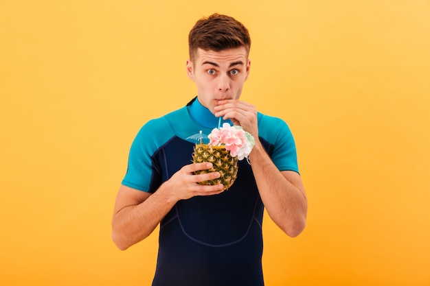 Image of surprised surfer in wetsuit drinking cocktail and looking at the camera