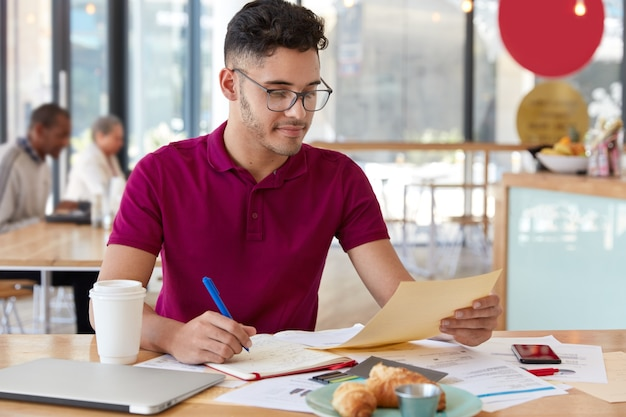 Image of teenage boy with trendy haircut, wears optical glasses, makes records in notepad, holds paper, uses modern technology for distant work, poses against cafe interior, develops new startup