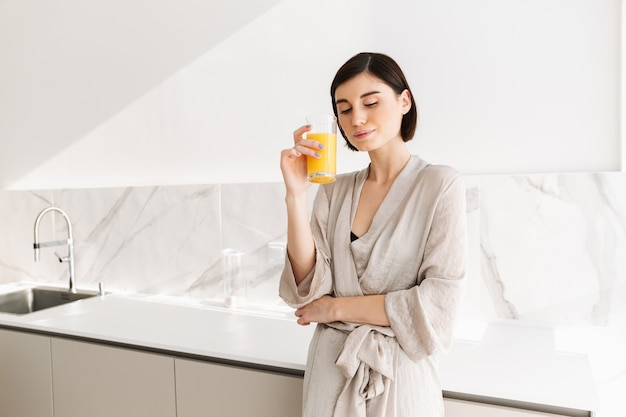 Image of tender brunette woman waking up in morning and drinking orange juice from transparent glass, in white kitchen