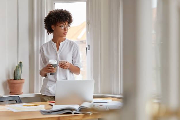 Image of thoughtful ethnic young woman focused aside, goes through some paperwork at home