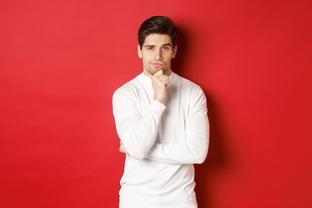 Image of thoughtful handsome man making assumption thinking and looking at camera standing in white ...