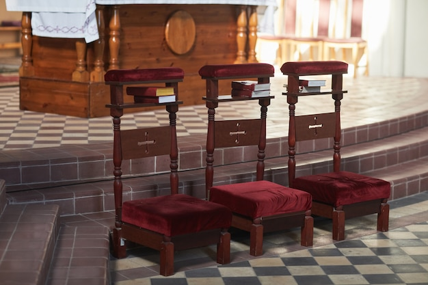 Image of three chairs standing in a row in empty catholic church