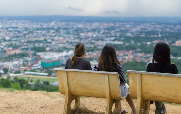 The image of three women who looking at the city view from the height.