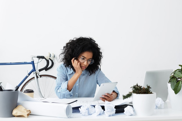 Image of tired upset young african woman feeling fed up and sleepy while working from home