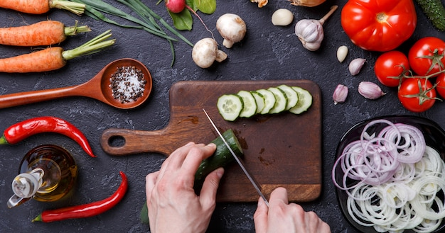 Image on top of fresh vegetables, mushrooms, cutting board, oil, knife, hands of cook