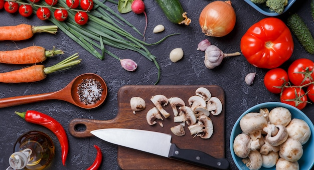 Image on top of fresh vegetables, mushrooms, cutting board, oil, knife