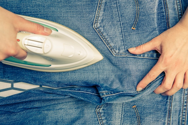 Image on top of man ironing blue jeans on ironing board