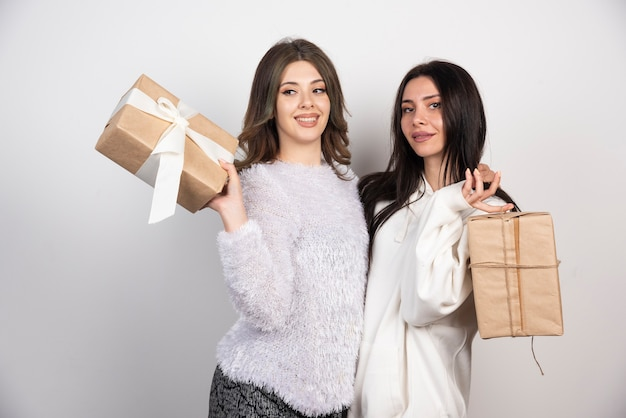 Image of two best friends standing together and holding gift boxes .