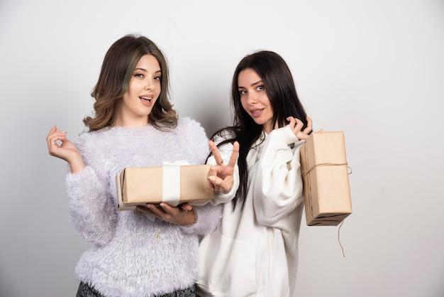 Immagine di due migliori amici in piedi insieme e in possesso di scatole regalo.