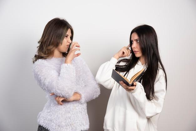 Immagine di due migliori amici in piedi insieme e in posa con il libro sul muro bianco.