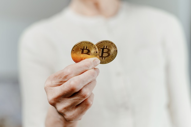 Image of two bitcoins in the hands of a woman