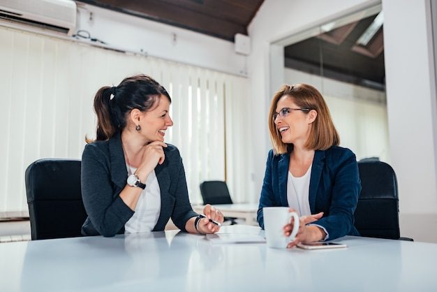 Image of two business woman talking in bright office.