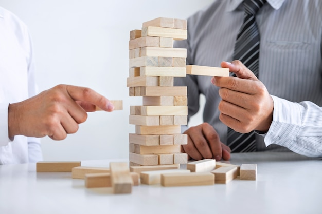 Image of two businessman hand placing making wooden block structure growing up the tower