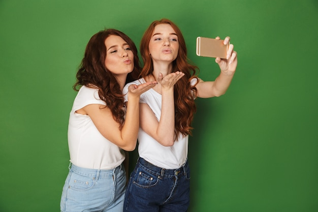 Image of two flirty women with ginger hair taking selfie on smartphone and blowing air kiss on camera, isolated over green background