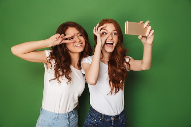 Image of two funny teen girls with ginger hair showing ok and peace sign near eyes, while taking selfie on cell phone isolated over green background