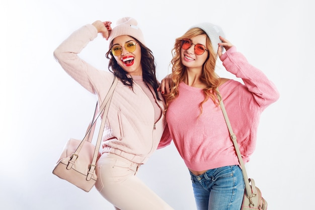 Image of two girls, happy friends in stylish pink clothes and hat spelling funny  the together. white background. trendy hat and glasses.showing peace.