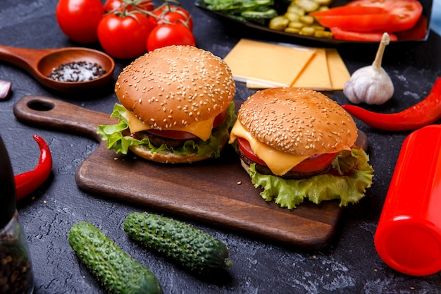 Image of two hamburgers on wooden board, cheese