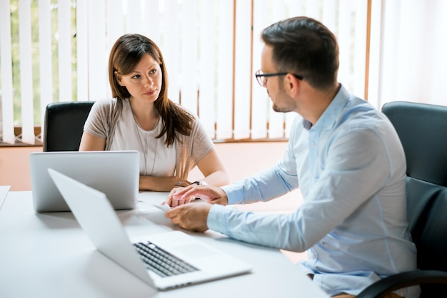 Image of two young business partners talking in office