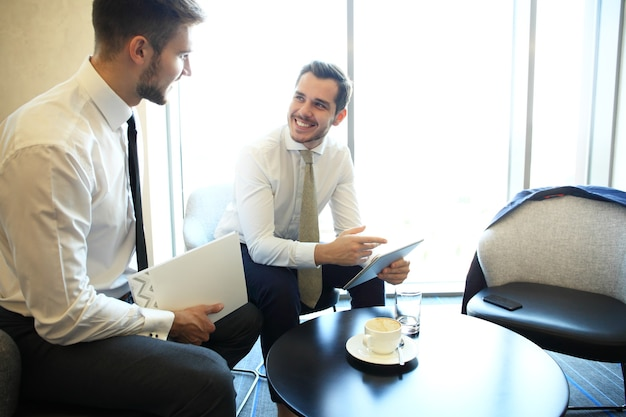 Image of two young businessmen using touchpad at meeting.
