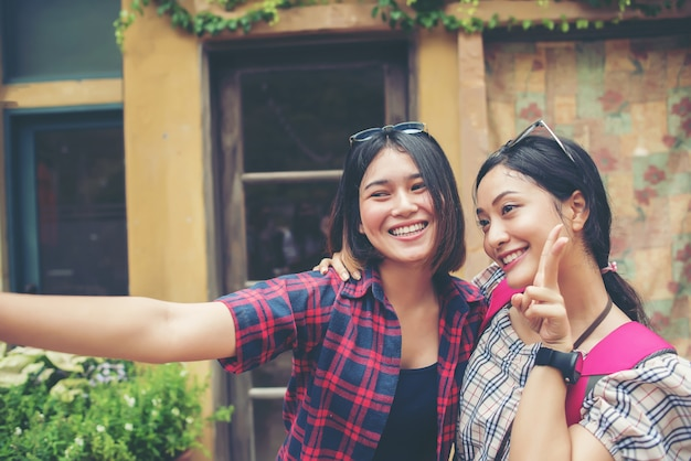 Image of two young happy women friends standing in urban city. taking selfie together.