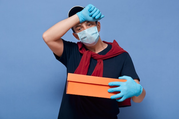 Image of unhappy ill infected young delivery man wiping out sweat from forehead, looking aside, holding parcel in one hand, having fever, symptoms of coronavirus.