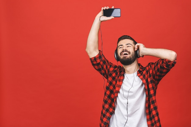 Image of unshaved man 30s singing while listening to music with earphones and mobile phone isolated over red wall.