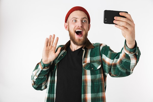 Image of unshaved man wearing hat and plaid shirt taking selfie photo on cell phone, while standing isolated over white background