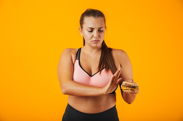 Image of upset chubby woman in tracksuit doing stop gesture while holding sandwich, isolated over yellow background