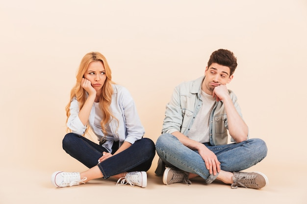 Image of upset man and woman sitting on the floor with in lotus pose and propping their heads while pouting after fight or quarrel, isolated over beige wall