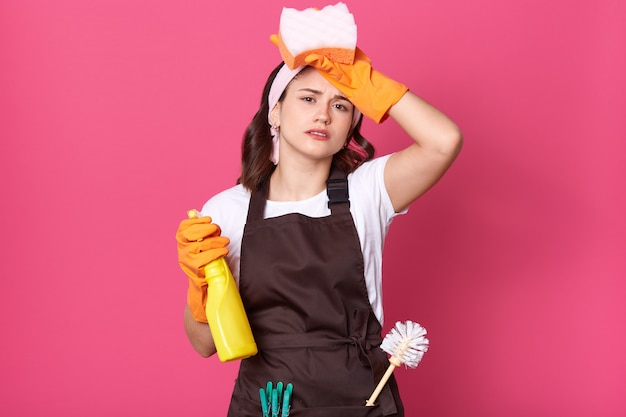 Image of upset tired housewife dresses brown apron with plunger and pins in pocket