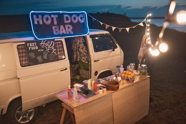 Image of van with outdoor bar with food and drinks decorated with lights at beach party
