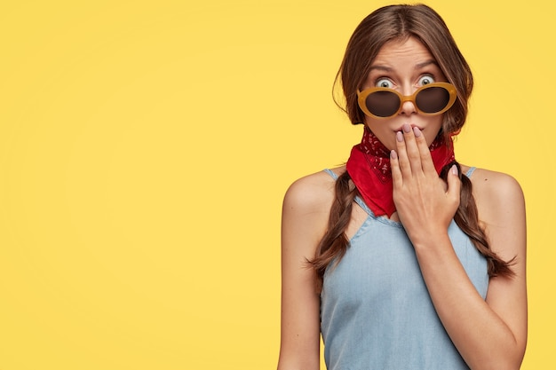 Image view of surprised dark haired woman covers mouth with hand, wears trendy shades, red bandana, looks with popped eyes
