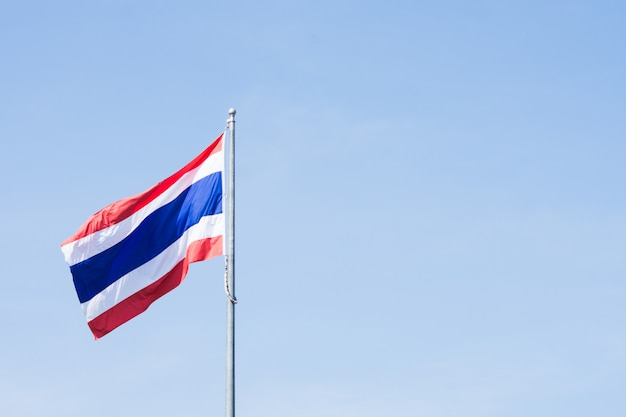 Image of waving thai flag of thailand with blue sky.
