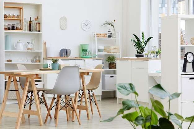 Image of white modern kitchen with big table and modern chairs in the house