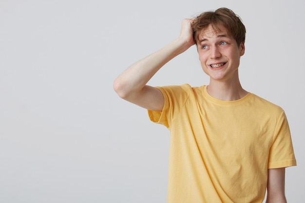 Image of white young male standing over white wall looks aside with broad smile, wears yellow bright t-shirt and has braces on his teeth. isolated over white wall with copy space