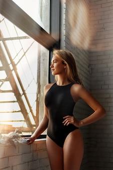 Изображение с молодой блондинкой в теле, смотрящей в окно