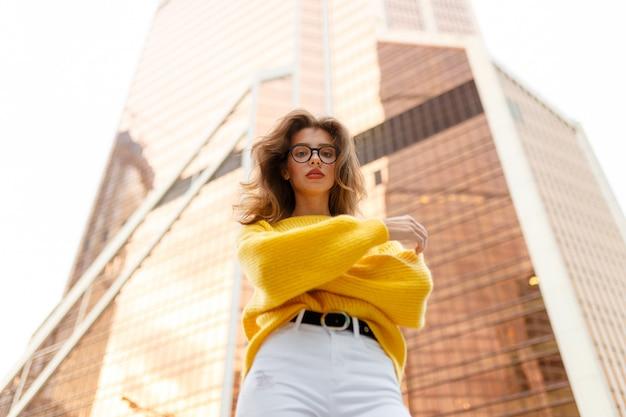 産業用建物の背景に逆さまに見ている若いブルネットの女性の画像