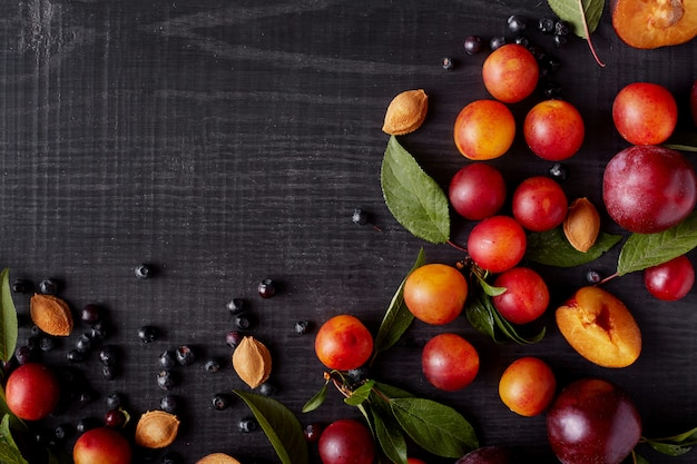Image with beautiful composition of blueberries, plums, aliches and green leaves on dark concrete surface. delicious friut on dark surface. top view. halthy eating concept. copy space for promotion