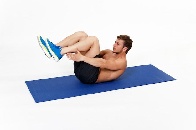 Image with a strong, fit, athlete young man doing abs exercises