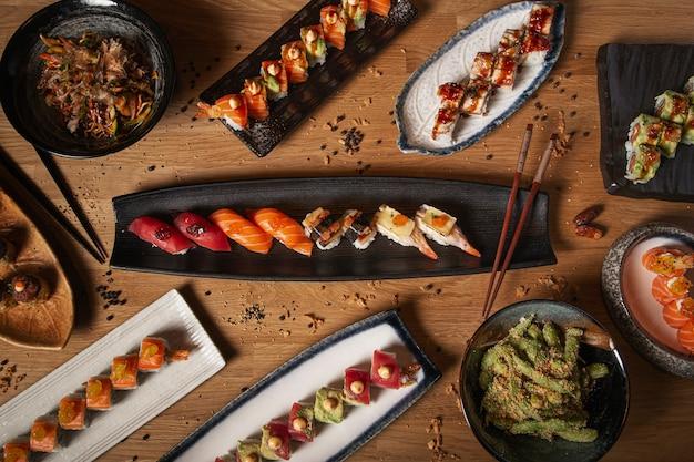 초밥, 사시미, 초밥, 야키소바, 완두콩 등 다양한 요리가 레스토랑 테이블에있는 이미지