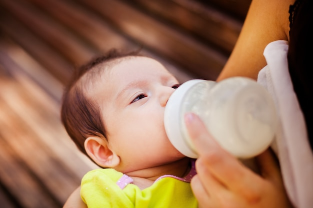 Image of the woman feeding baby from children's small bottle