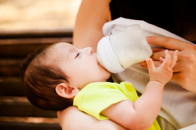 The image of the woman feeding her baby from a children's small bottle