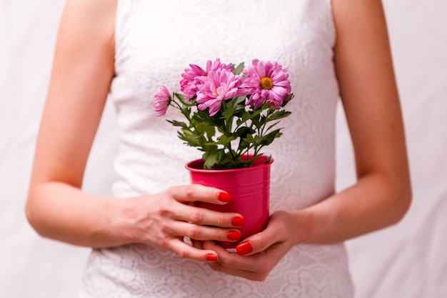 Image of woman holding pot with pink flower